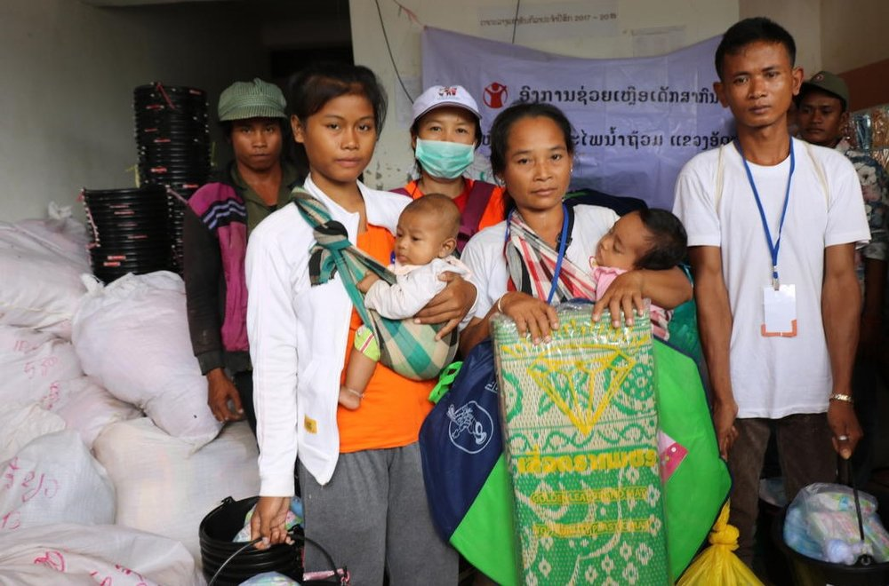 Above: A Lao family receives emergency supplies at an evacuation centre. Photo credit: Save the Children.
