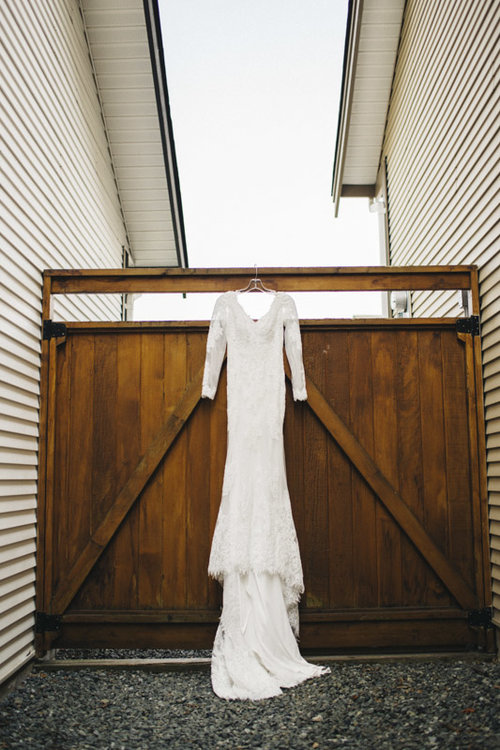 wedding dress hanging off of a fence
