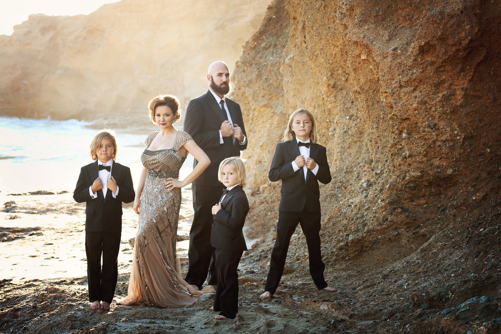 A formal family beach portrait with three boys, mom, and dad.  All dressed formally in tuxedos and an evening gown for this fine art photography