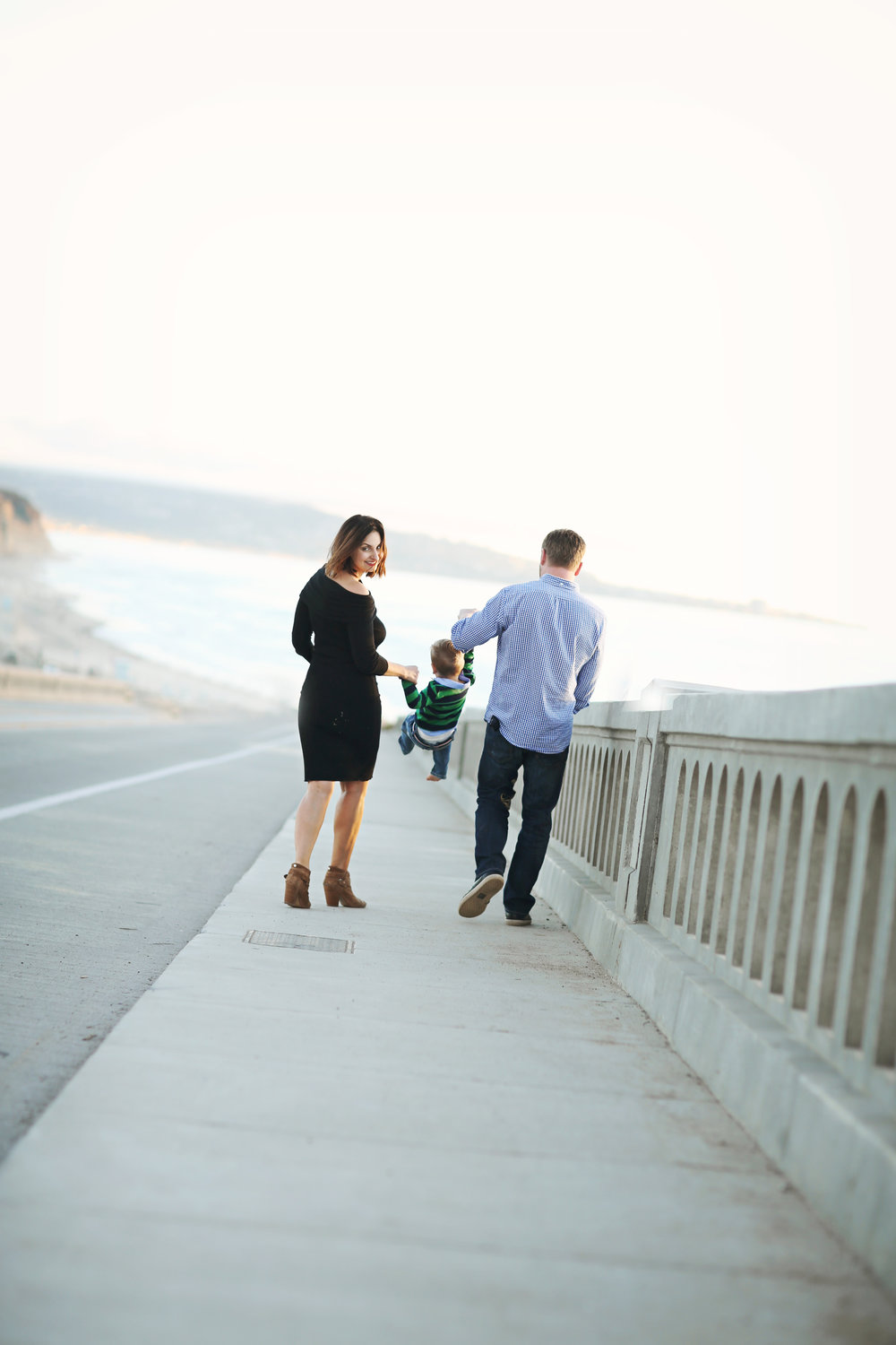Fine art photo of a family walking across a bridge in orange county.  A beautiful beach portrait at San Clemente Beach.