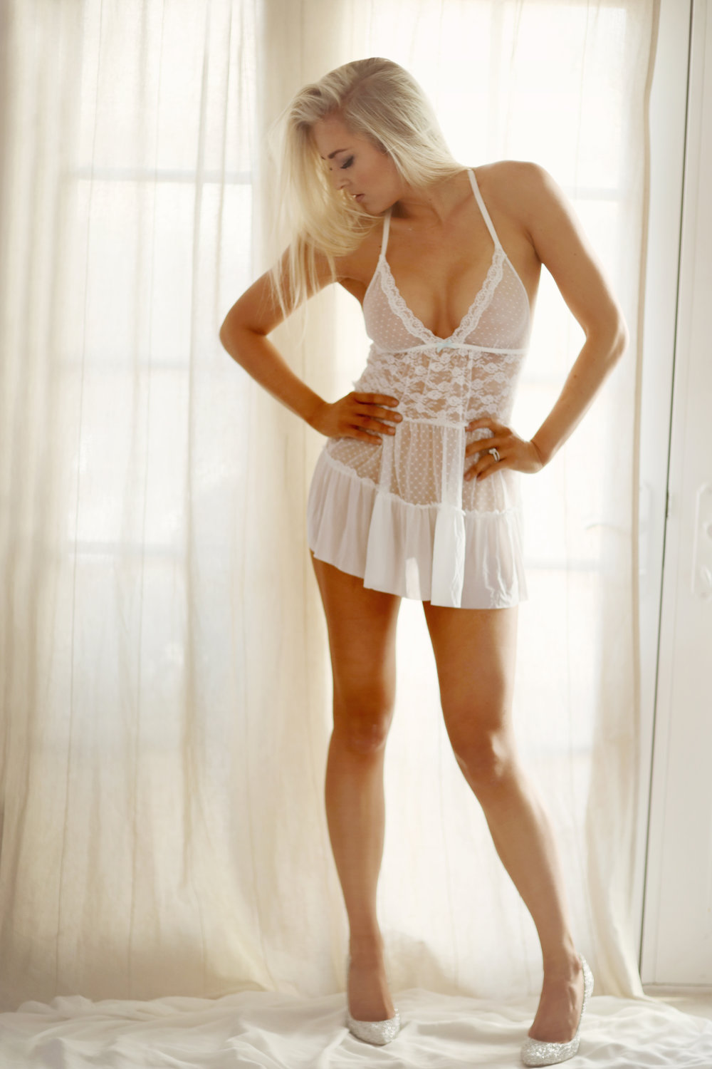 Girl wearing a white see through skirted teddy and white high heels for her boudoir portrait.