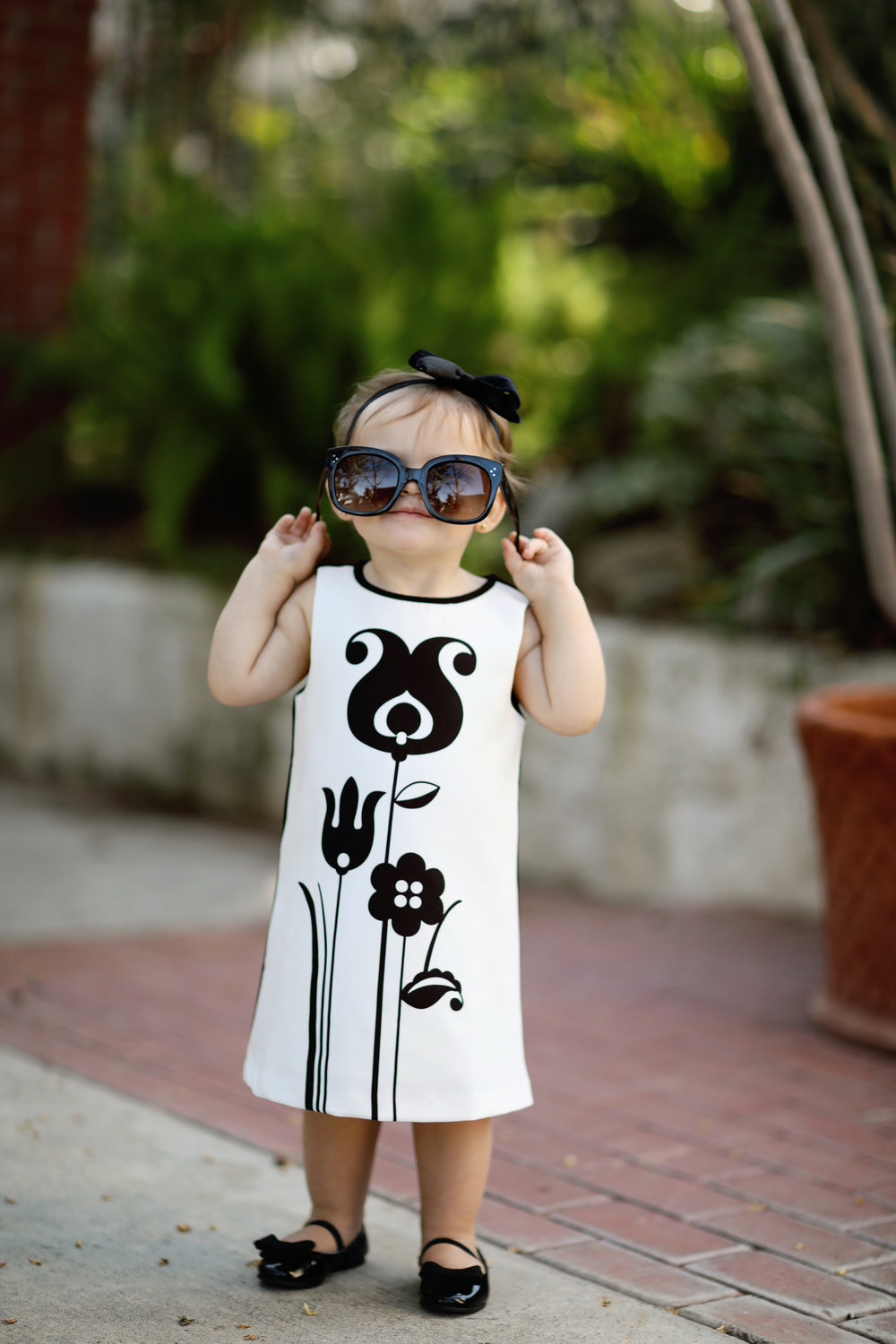 daughter of fashion blogger.  Toddler in black and white dress.  Fine art photo
