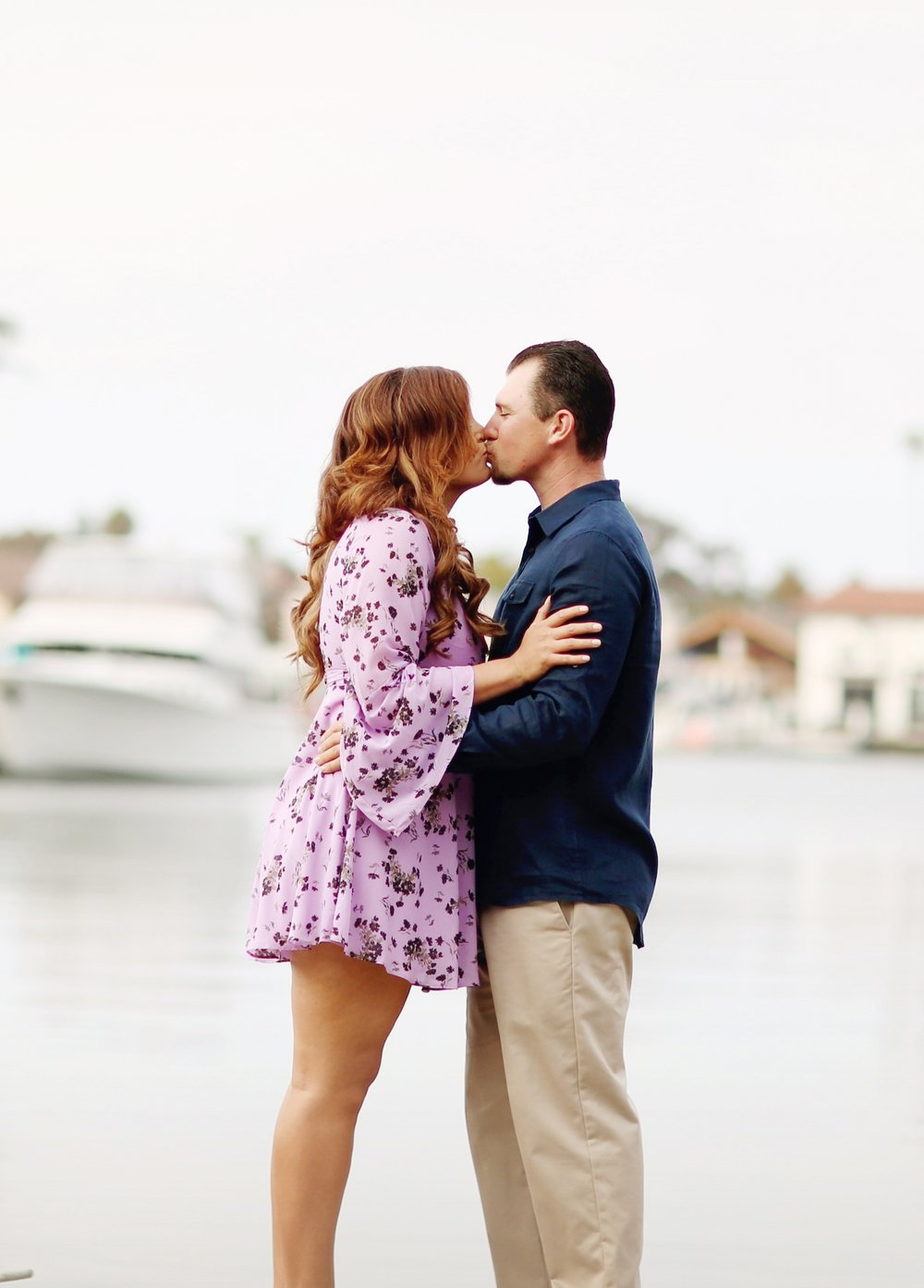 Boats, beach, engaged couple kissing in this beautiful beach portrait.