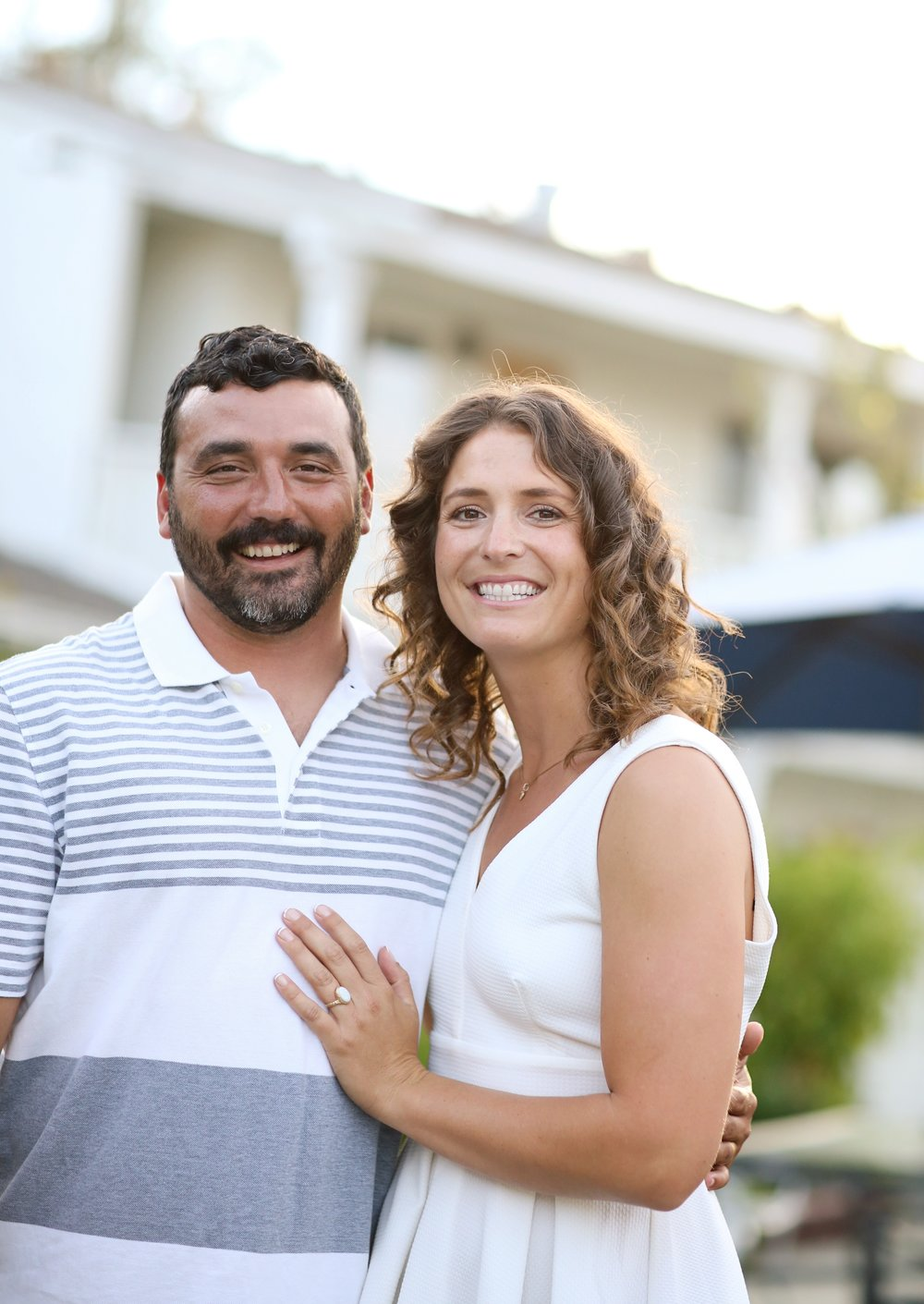 Standing in front of a cottage at the beach in Orange County is an engaged couple posing for their beach portrait.