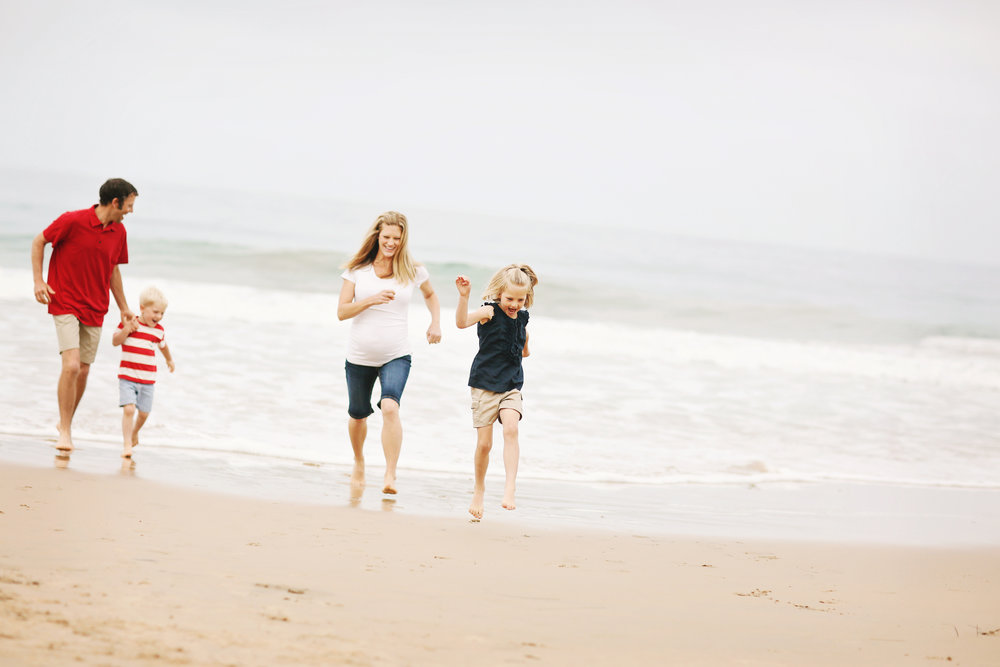 Family running on the shoreline at the beach for a fine art family portrait.