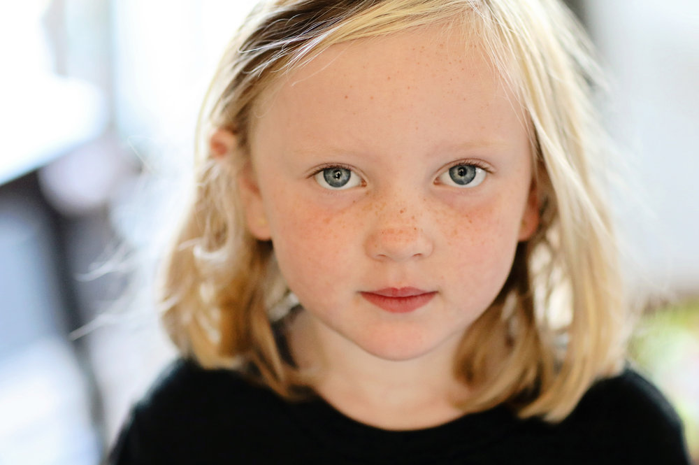 Young girl with blond hair and piercing eyes portrait.  Fine art photography