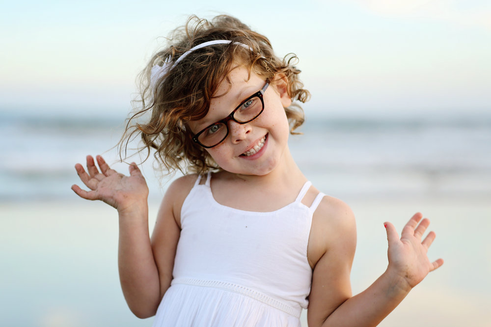 young girl on the beach wearing glasses in San Clemente, Orange county. Beach portrait