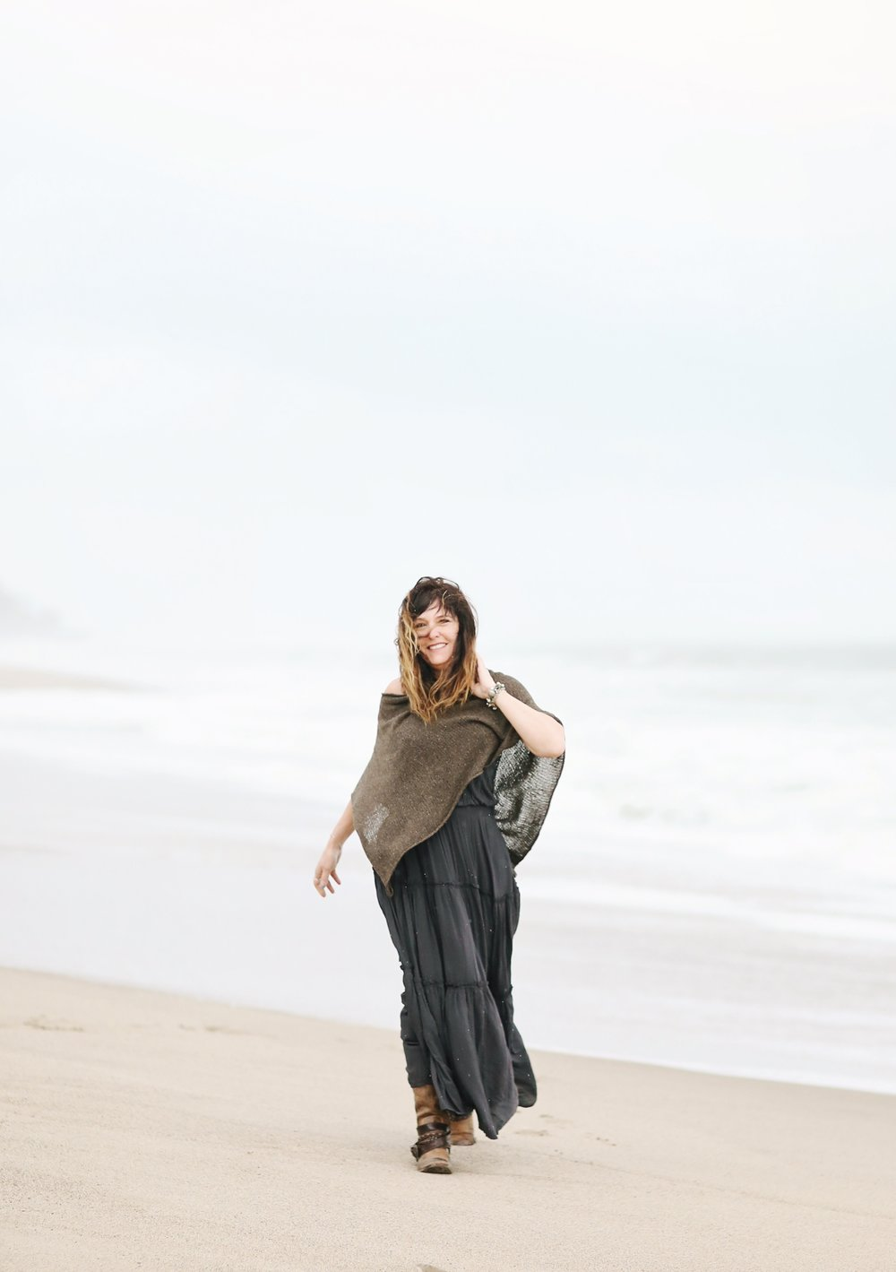 Fine art image of woman walking on the beach in the breeze.  Beach portrait.