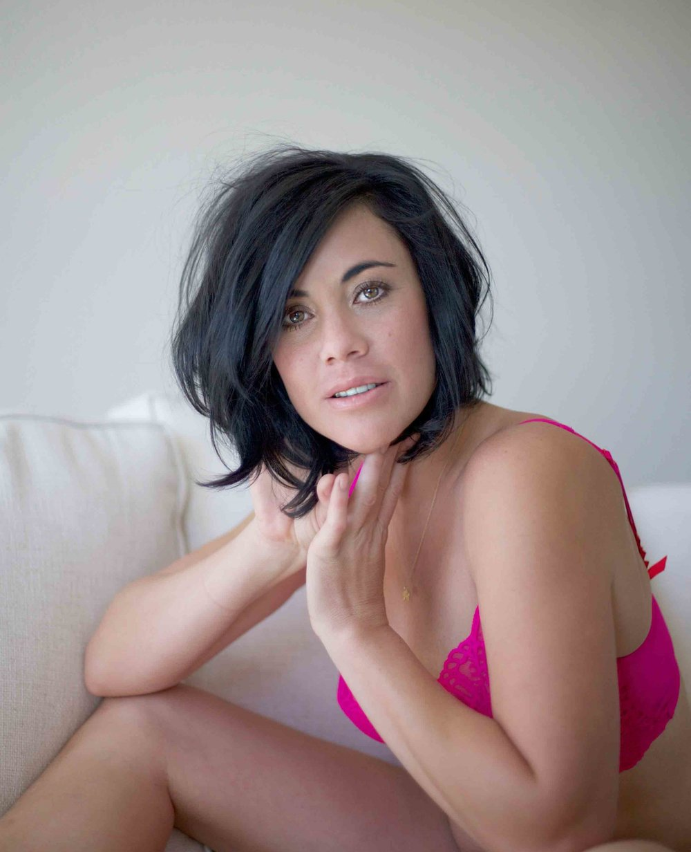 Beautiful dark haired girl posing in pink bra for a boudoir photo shoot.