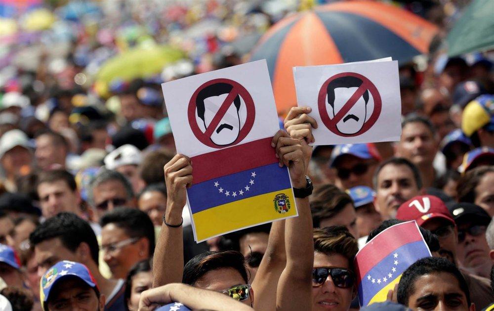 Protestors holding anti-Maduro signs in Caracas, Venezuela.