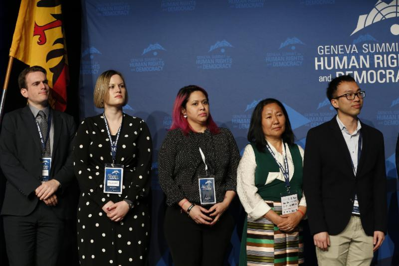 "After awarding the ""Women's Rights Prize,"" RWCHR Director of Policy and Projects, Brandon Silver, and human rights defenders look on as the Laureate delivers her acceptance speech."