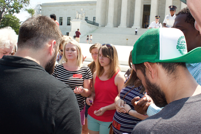 Following the ruling, Matt Lockett leads a group in prayer and communion outside the Supreme Court (Photo: Josh Shepherd)
