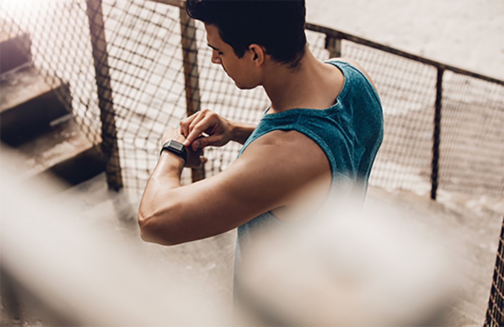 Man in blue tank top checking FitBit near stairs and fence
