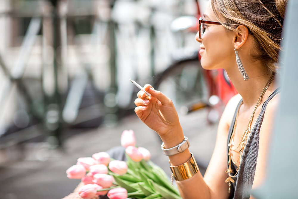 Woman smoking marijuana cigarette smiling and wearing jewelry