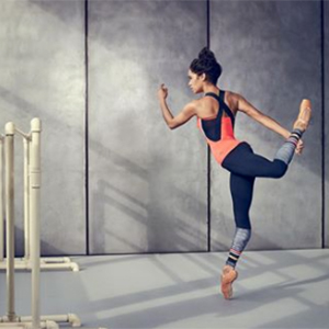 Woman stretching while standing on one leg balancing on toes in grey room