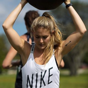 Alex Silver-Fagan Instagram model wearing white Nike tank top holding weight above head