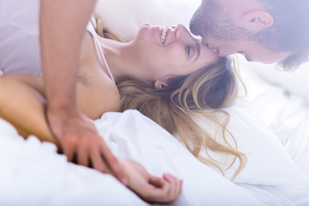 Man kissing smiling woman in bed with white sheets