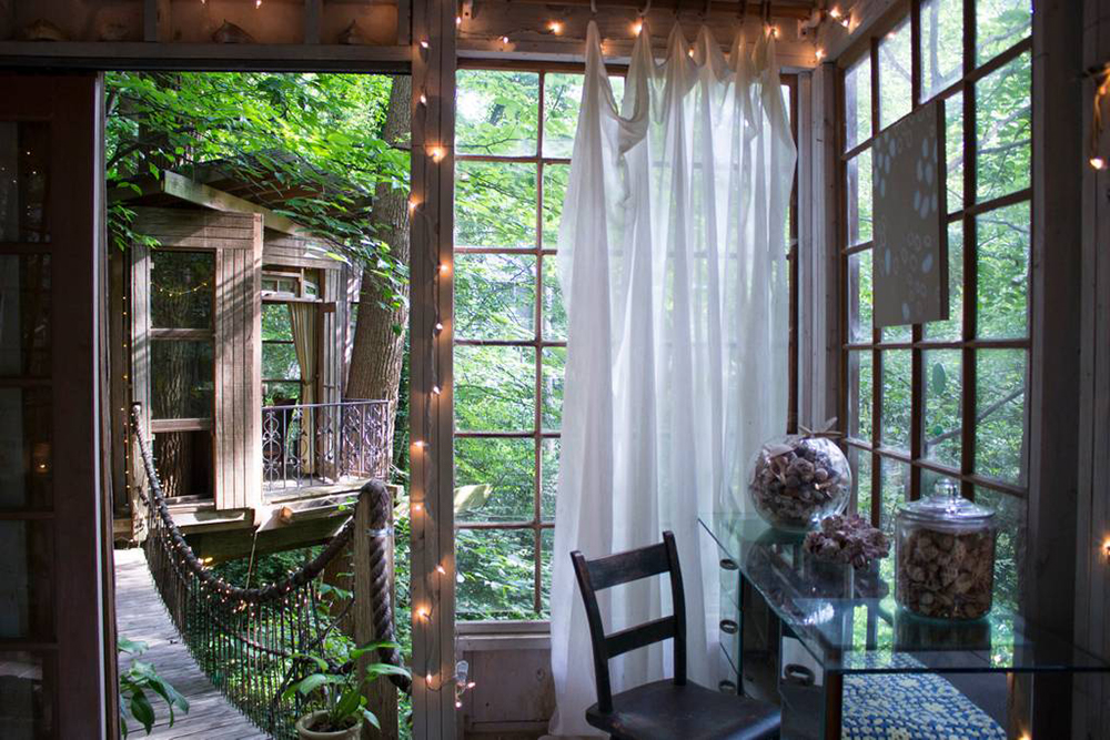 multi room airbnb treehouse in a lush green forest with Christmas lights white curtains and rope bridge