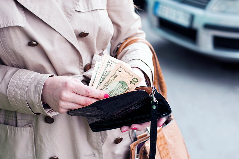 Woman in tan overcoat with pink fingernails removing ten dollar bills from black purse