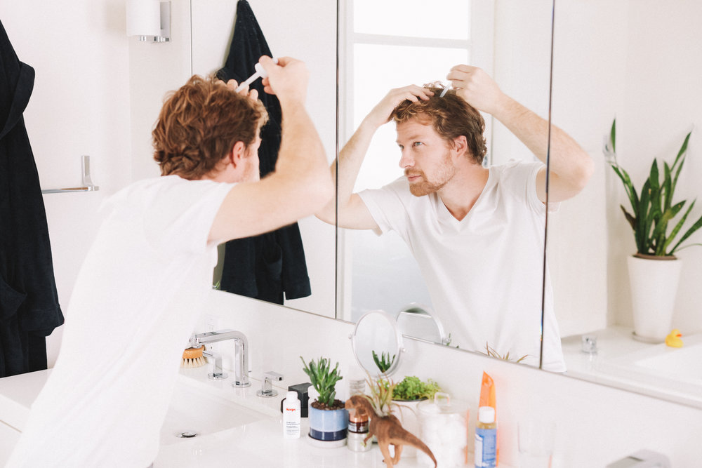 Man applying Keeps hair loss serum in mirror