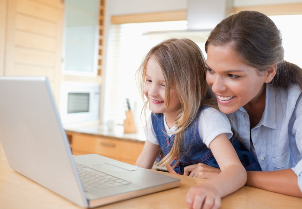 Mom and daughter on laptop using Hooked on Phonics