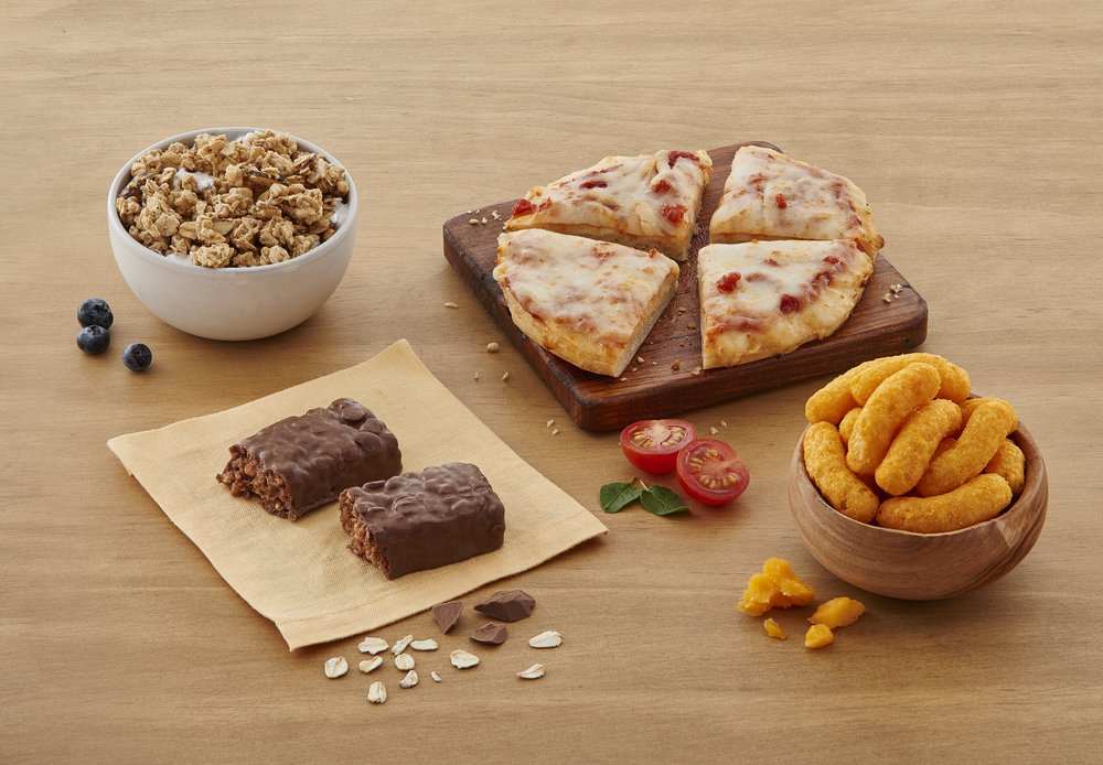 Nutrisystem pizza, granola, chocolate bar, cheese puffs, and tomatoes