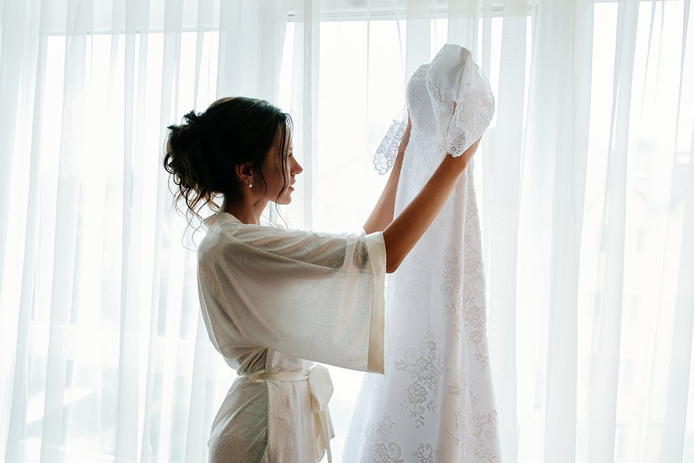 Woman-holding-and-looking-at-wedding-dress.jpg