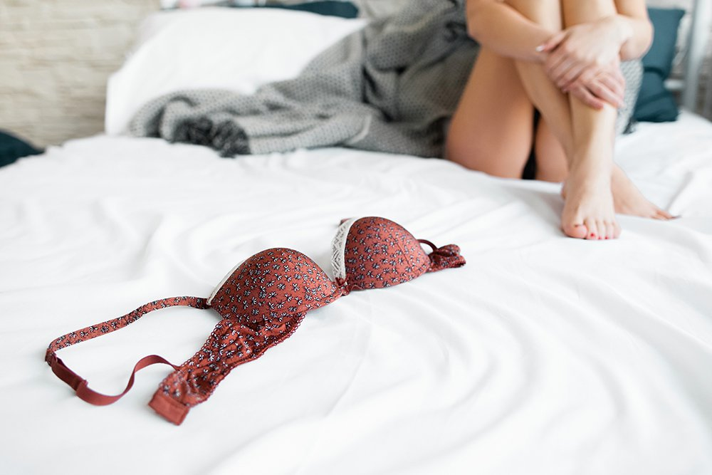 Woman-sitting-on-bed-with-bra.jpg