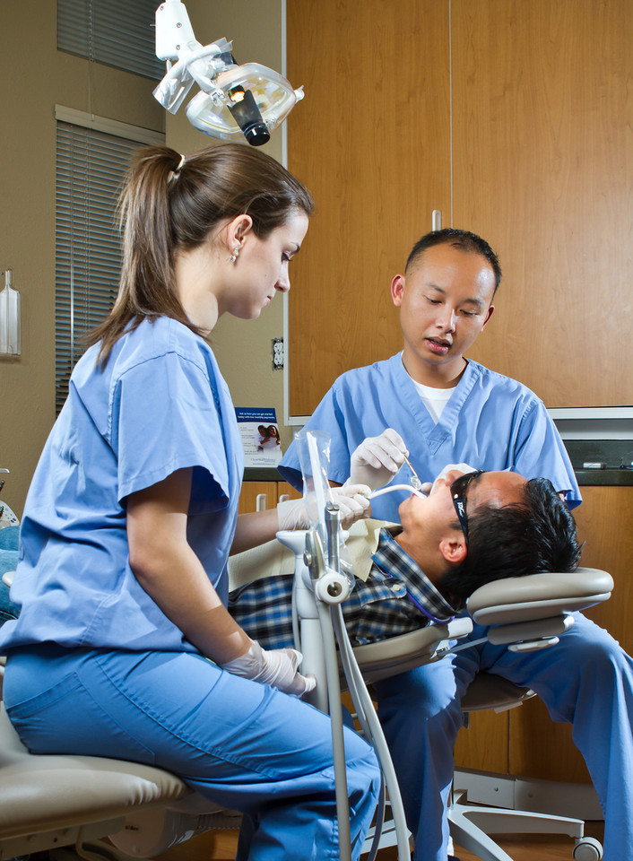 Dr. Pribadi and team providing an exam to a patient in dentist chair.