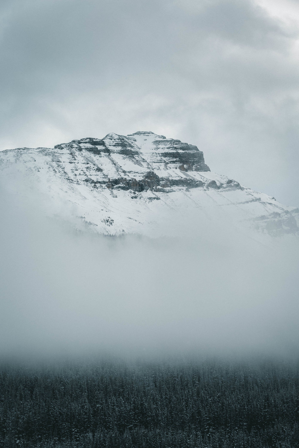 14 | Rising from the fog - Going up the mountain between Banff and Yoho, I was welcomed by snowy forests and peaks. I stopped on the side of the road in a closed parking lot to grab a shot of the side of the mountain with snowy trees coming out of the fog. I did take that shot. But a minute later, the fog cleared out for a brief instant, revealing the peak. I shot again. Few instants later, the peak went hiding back in the fog. Canadian Rockies, October 2018.