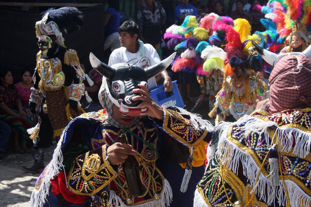 Two young K'iche' bull-masked dancers taking a beer break during a  Baile de los Toritos . Note the ornately-costumed, black-masked figure walking behind. Both bulls and black house servants are common themes across all the bullfight and related dances in western Guatemala.
