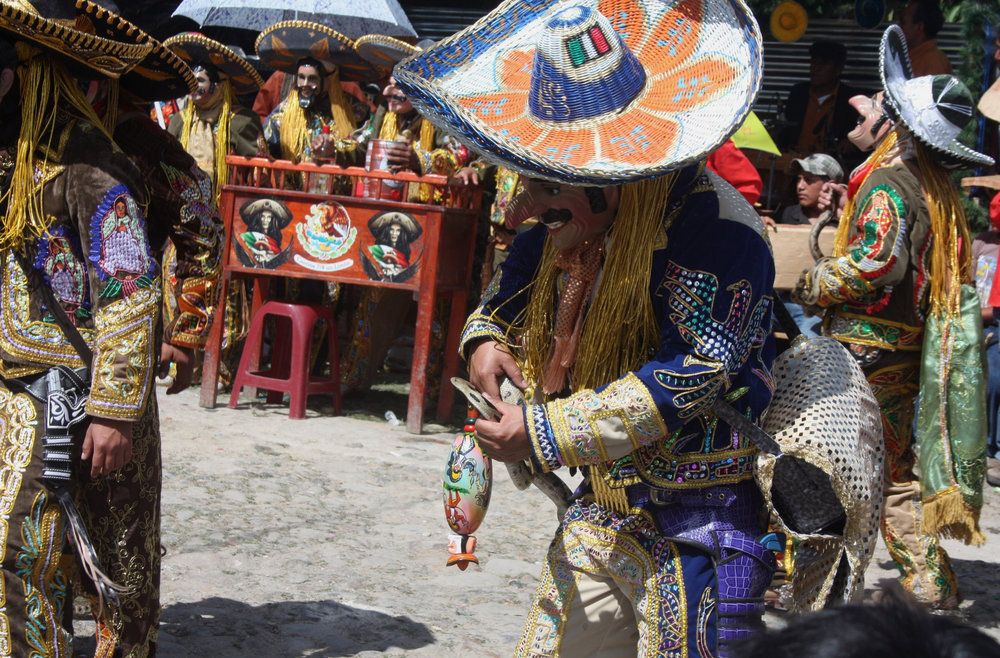 Dancers with adult bullsnakes. Notice the relaxed grip that they have on the animals. This careful handling technique, that permits fairly unrestricted movement by the snake, minimizes bite risk. This dancer's painted gourd rattle (inverted in this photo) shows cowboys with lariats and live snakes. Also note the well-attended open bar in the background.