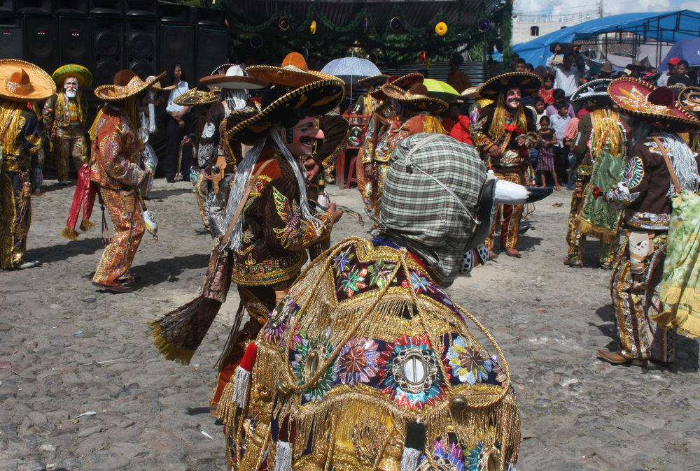 The bull makes his entrance front and center in  El Baile de los Mexicanos . Note the old, white-bearded  Patrón  hiding away rear left.