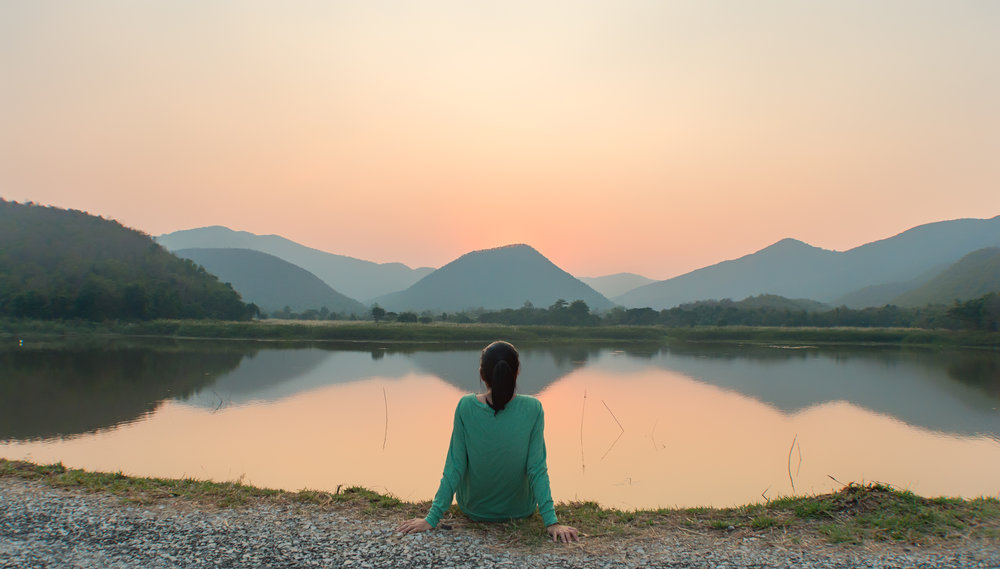 stock-photo-a-woman-is-sitting-at-ease-by-the-lake-during-sunset-moment-552045823.jpg