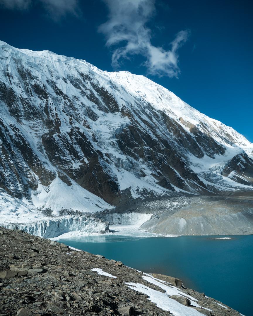 Järveä ympäröi lumipeitteiset vuoret.