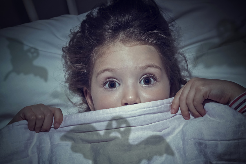 scared cute little girl under the blanket in her bed