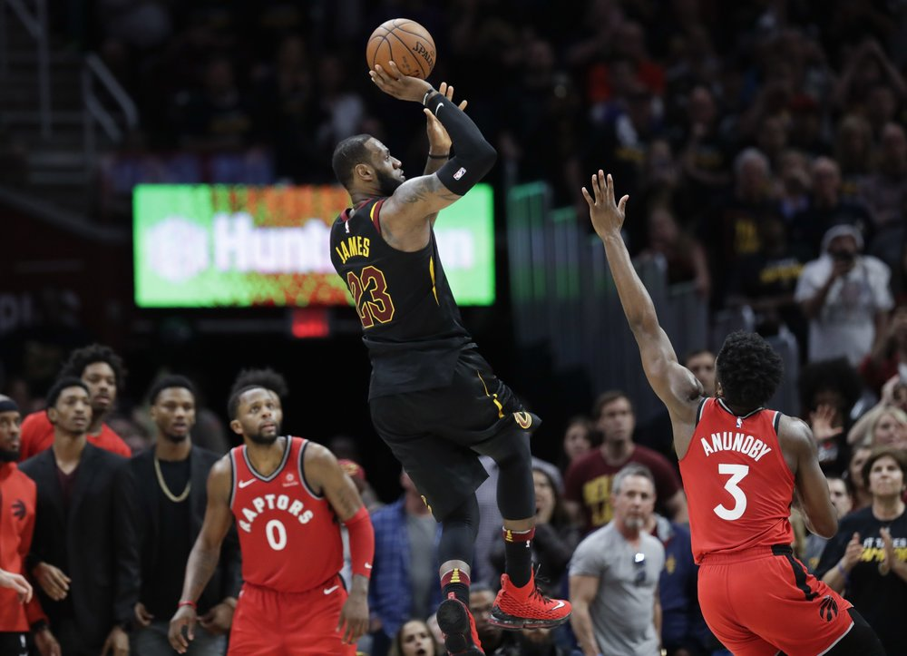 Cleveland Cavaliers' LeBron James (23) hits the game-winning shot as Toronto Raptors' OG Anunoby (3) and CJ Miles (0) watch during the second half of Game 3 of an NBA basketball second-round playoff series, (AP Photo/Tony Dejak)