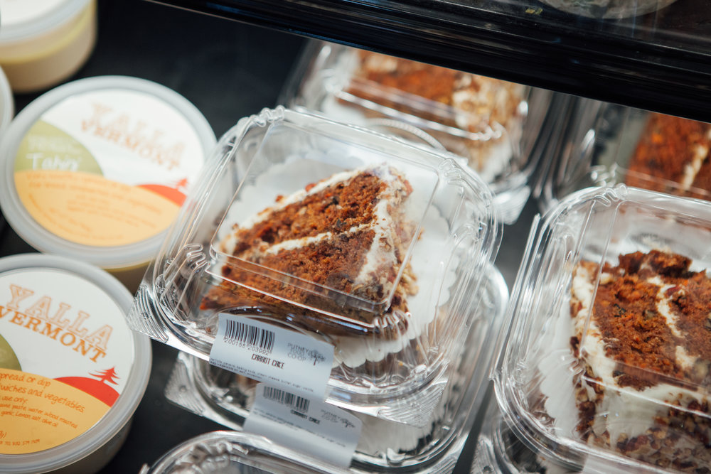 Thick slices of fresh carrot cake sits in the brand new Deli cold-case