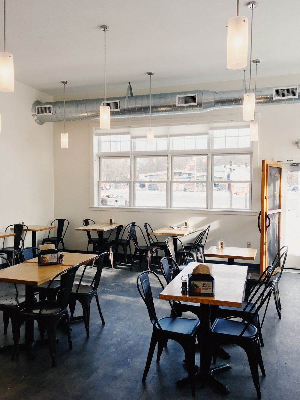 The cafe space when it first opened, featuring soft lighting and big sunny windows