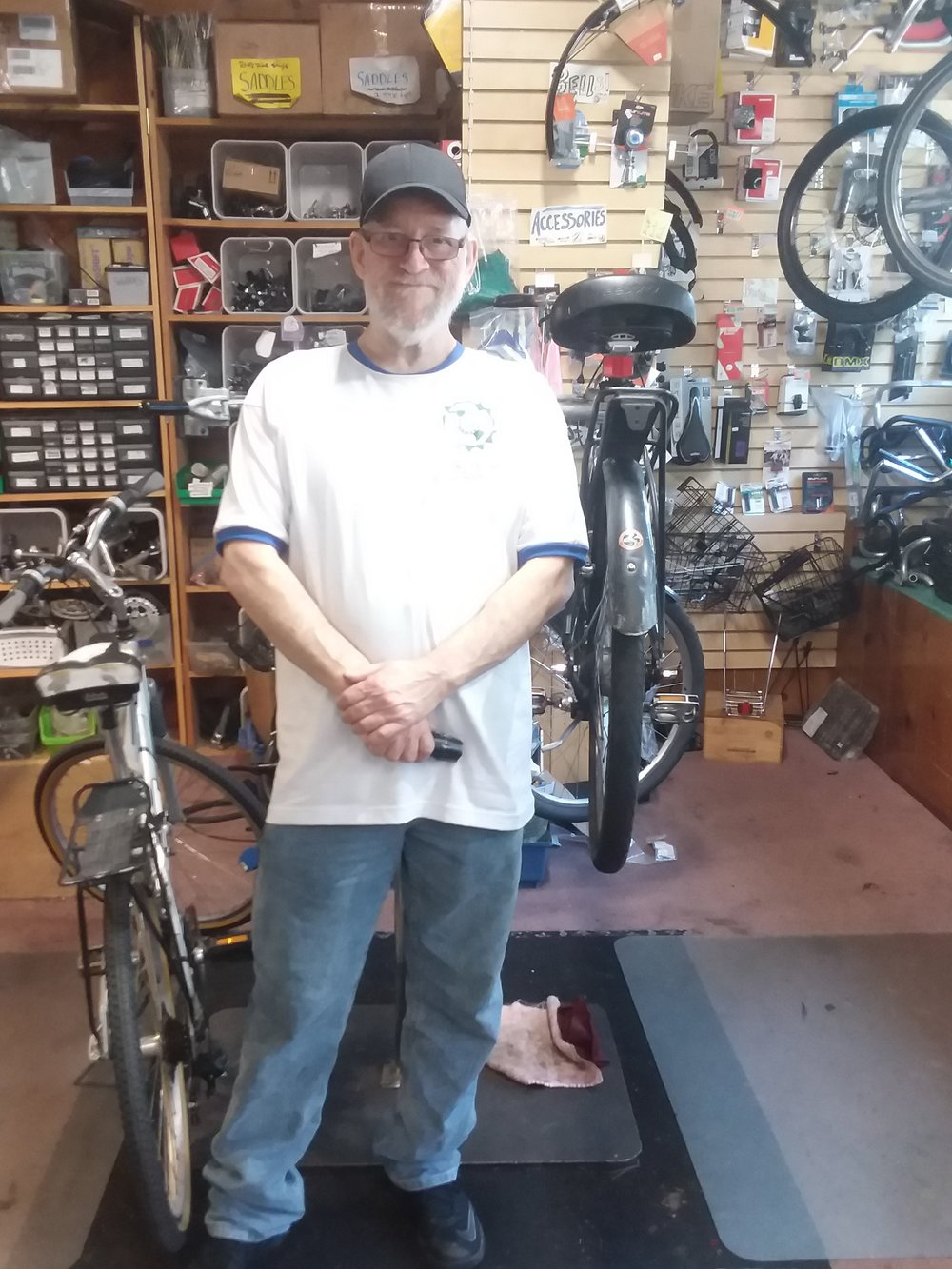 Image of Dave standing in the Bikes For Humanity PDX bike-shop in front of a bike stand. There is a bicycle to the right-hand side of the image and one suspended in the bike stand Dave is in front of.