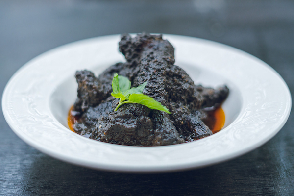Nguwa mbongo tchobi - A black spicy sauce with nguwa (pork)