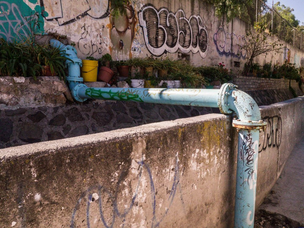This pipe carries water to thousands of homes in the Gabriel Hernandez neighborhood below. Pumps carry water up to the top of this hill only a few hours per day. Tinacos are often used as water storage devices and exhausted when pumps are turned off and no additional water is being delivered for the day.