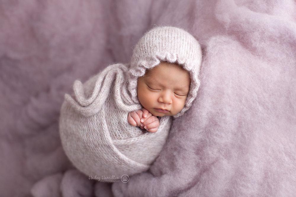 Newborn in pink knit potato sack wrap