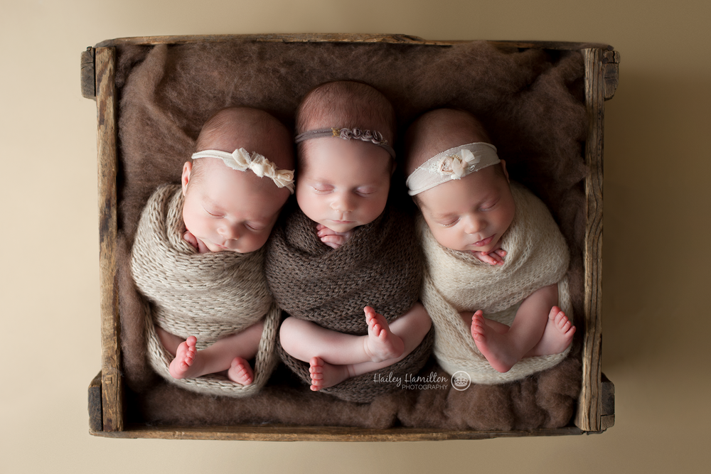 Triplet girls posed in box prop