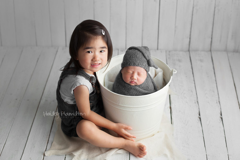 Newborn photo with young sibling