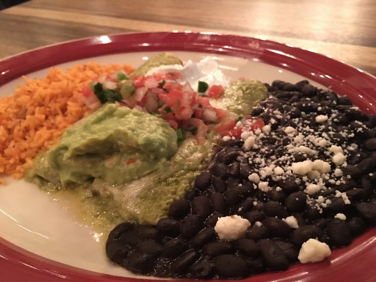 Pork enchiladas with poblano cream sauce, black beans and rice topped with guacamole and pico de gallo. Photo by Rachael Worthington.