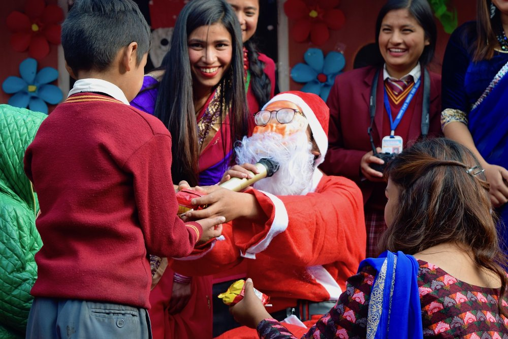 A Nepali Santa Claus giving treats to children following a school's Christmas show, December 2016.