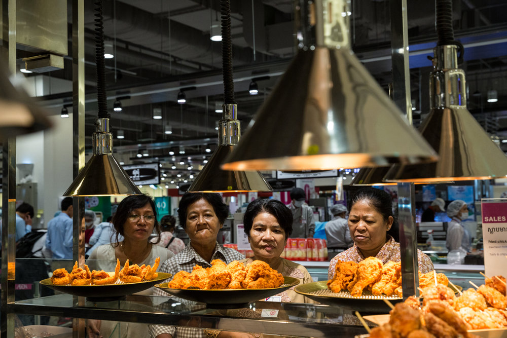 June 30, 2014 - Phnom Penh, Cambodia. Women look at the food on sale during the inaugural ceremony for Aeon mall, the first mega mall in Cambodia. The inauguration was attended by Cambodian Prime Minister Hun Sen and groups of residents from various economic backgrounds were trucked in to attend the event. © Nicolas Axelrod / Ruom