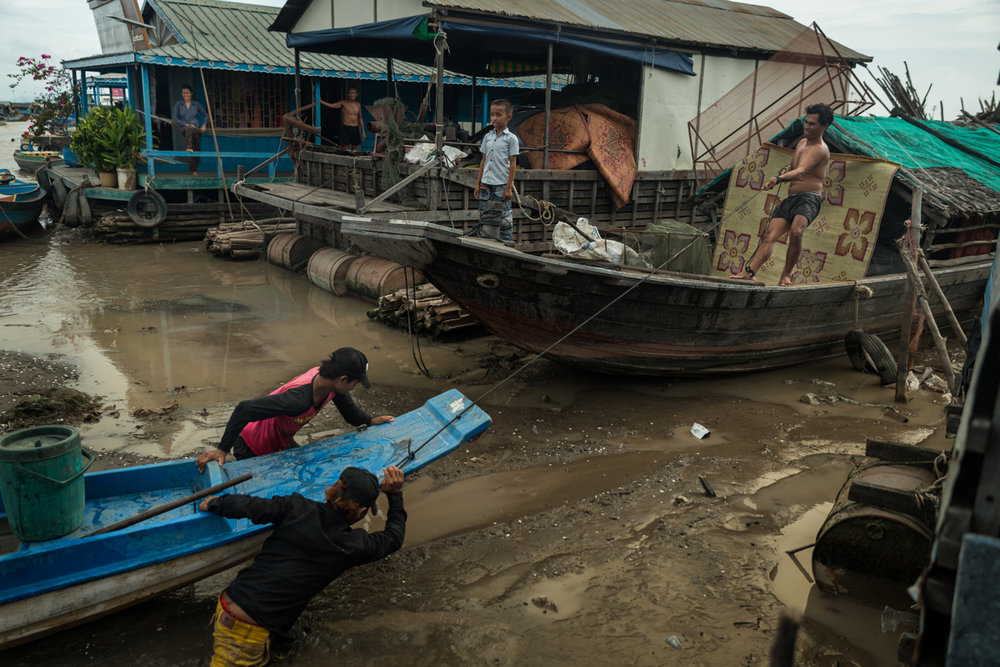 May 26, 2016 - Kampong Loung, Cambodia. A boat carrying goods is pushed up towards a storage barque. When the afternoon winds come from the east water levels drop on Kampong Loung making many floating homes only accessible by wading through deep mud. © Nicolas Axelrod / Ruom