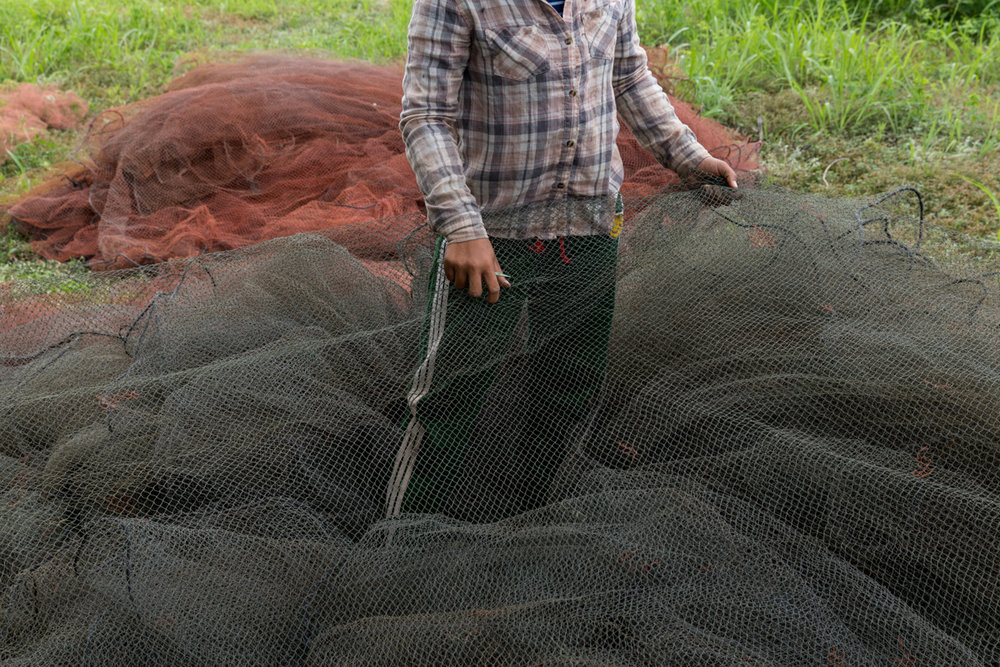 March 29, 2017 - Prek Tol, Cambodia. A fisherman sorts and repairs nets. © Nicolas Axelrod / Ruom